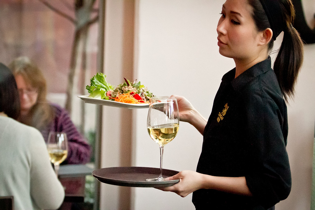 A server carries a salad and a glass of white wine to a table at Kacha Thai Bistro in Walnut Creek, Calif., on Friday April 7th, 2012.