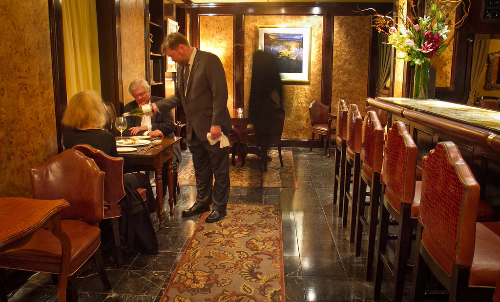 A waiter pours a glass of wine for customers in the bar at Keiko Restaurant in San Francisco, Calif., on Friday, January 20th, 2012.