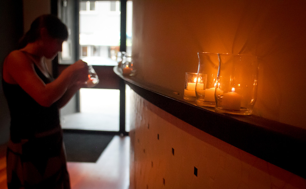 Lindsey MacDougall lights candles before Lolinda Steakhouse opens in San Francisco, Calif., on Friday, October 19th, 2012.