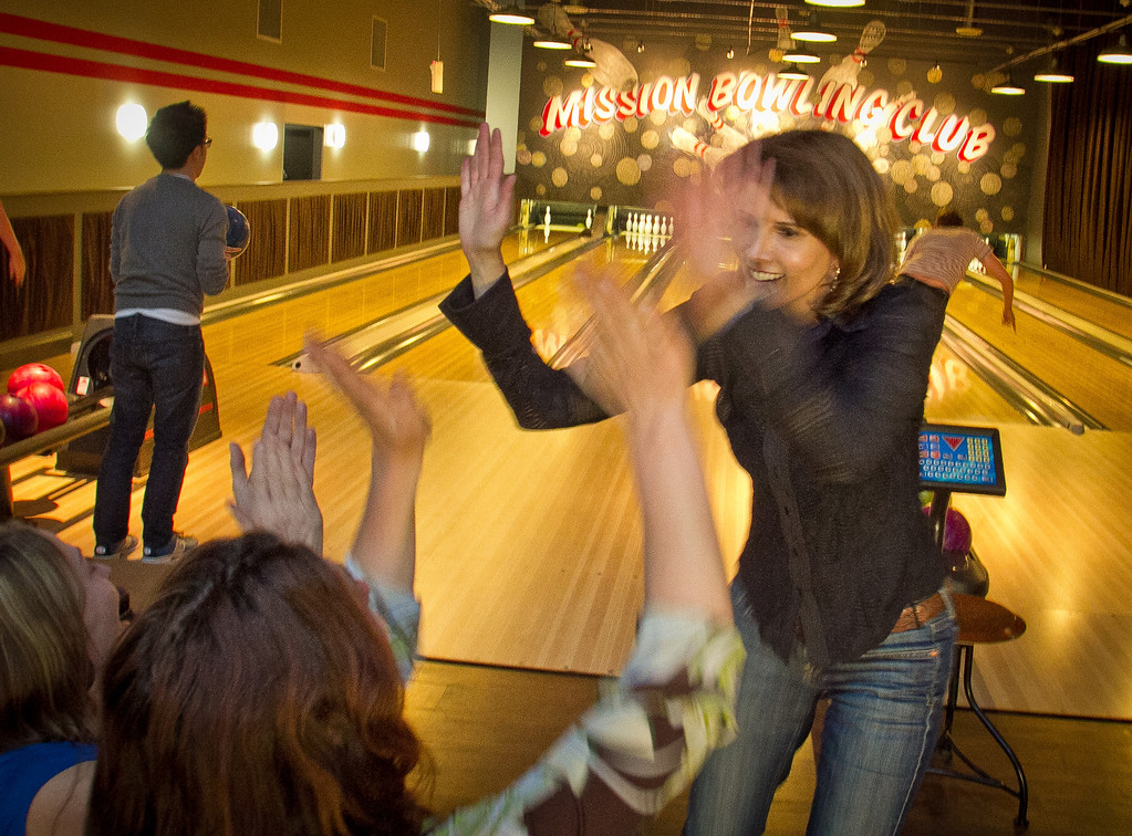 Leela Gil high fives her friends during their match at the Mission Bowling Club in San Francisco, Calif., on Friday, May 11th, 2012.