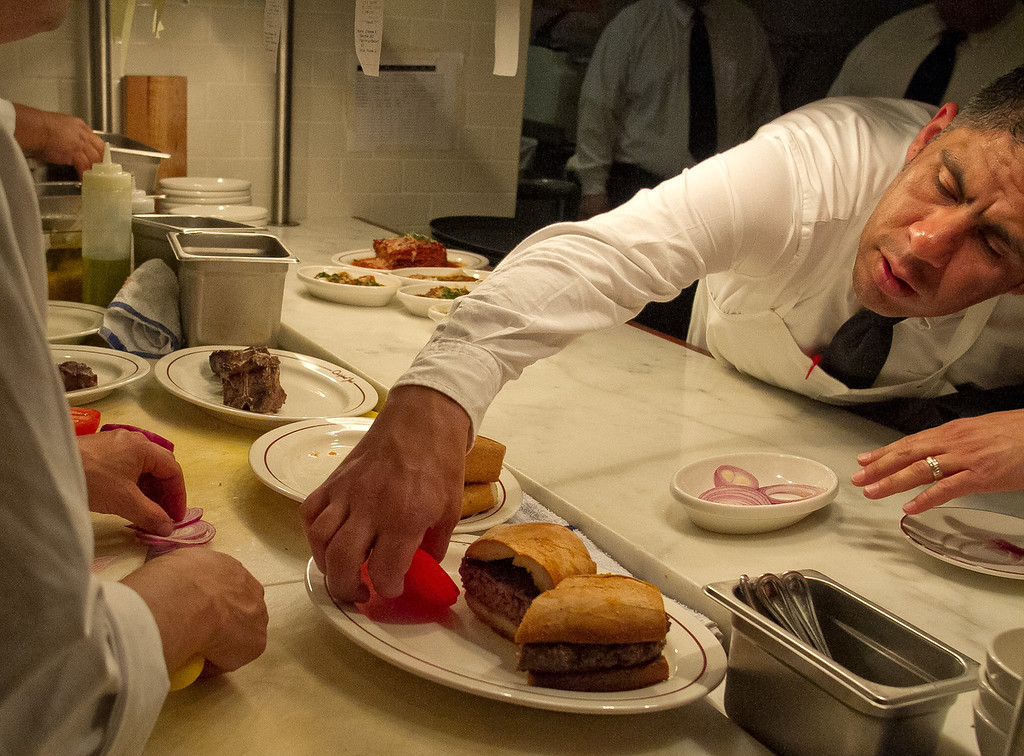 A server adds tomato to a Hamburger Sandwich at Original Joe's Restaurant in San Francisco,  Calif., on Tuesday, March 20th, 2012.