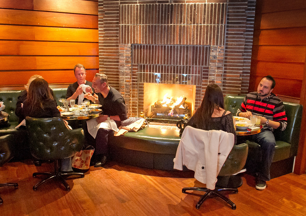 Diners enjoy dinner in front of the fireplace in the bar at Original Joe's Restaurant in San Francisco,  Calif., on Tuesday, March 20th, 2012.