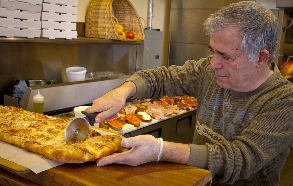 Owner Nicola Rivieccio cuts the Quattro Formaggio Pizza at PIQ Cafe in Berkeley, Calif., on Friday, February 17th, 2012.