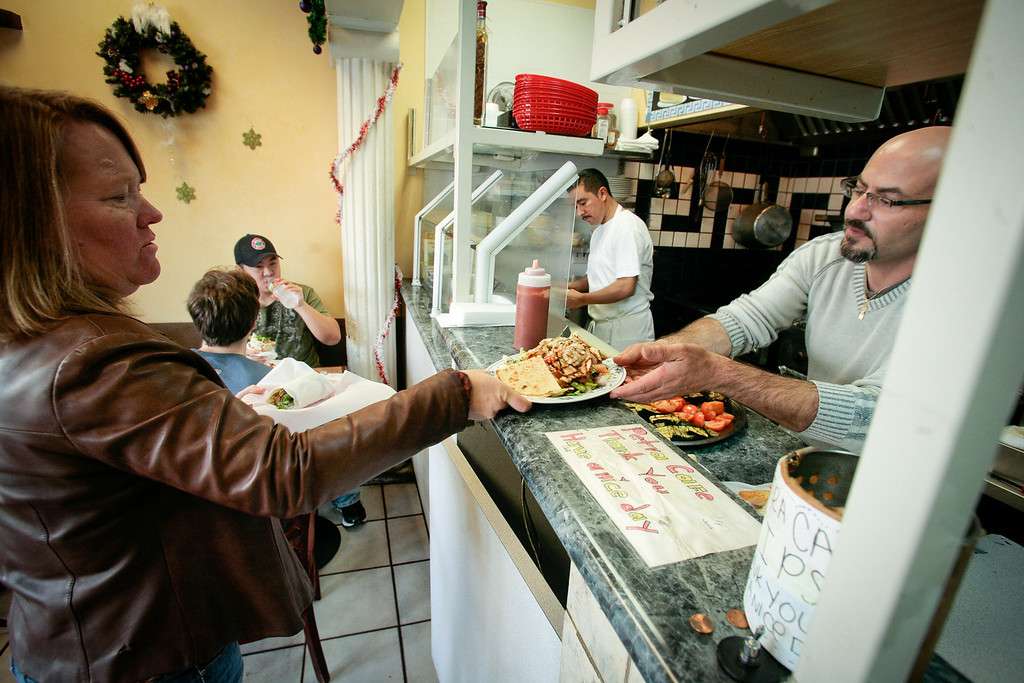 Owner of the Petra Cafe, Azmi Masarweh, hands food to a customer in Orinda, Calif., on Thursday, December 29th, 2011.