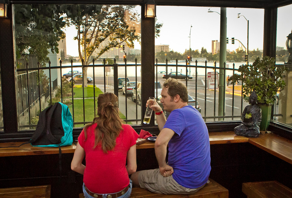 A couple enjoy a beer and the view of Lake Merritt on the patio at Portal Oakland in Oakland, Calif., on Tuesday,  August 28th, 2012.