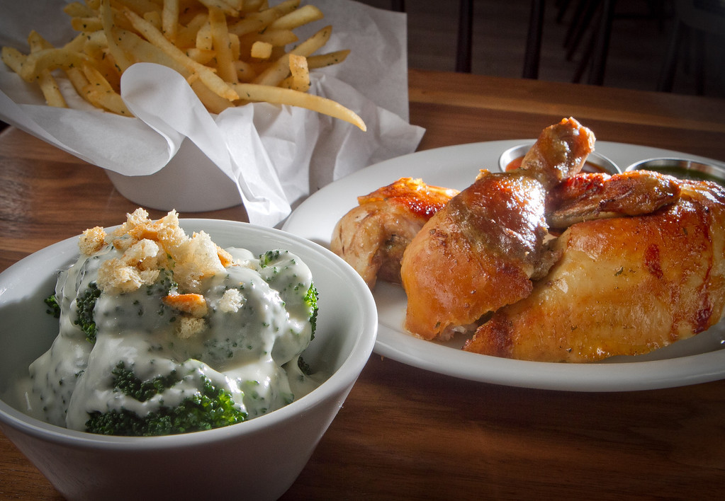 Broccoli with Cheese Sauce and the half rotisserie Chicken with fires on the side at Roostertail Restaurant in San Francisco Calif., is seen on Thursday, March 1st, 2012.