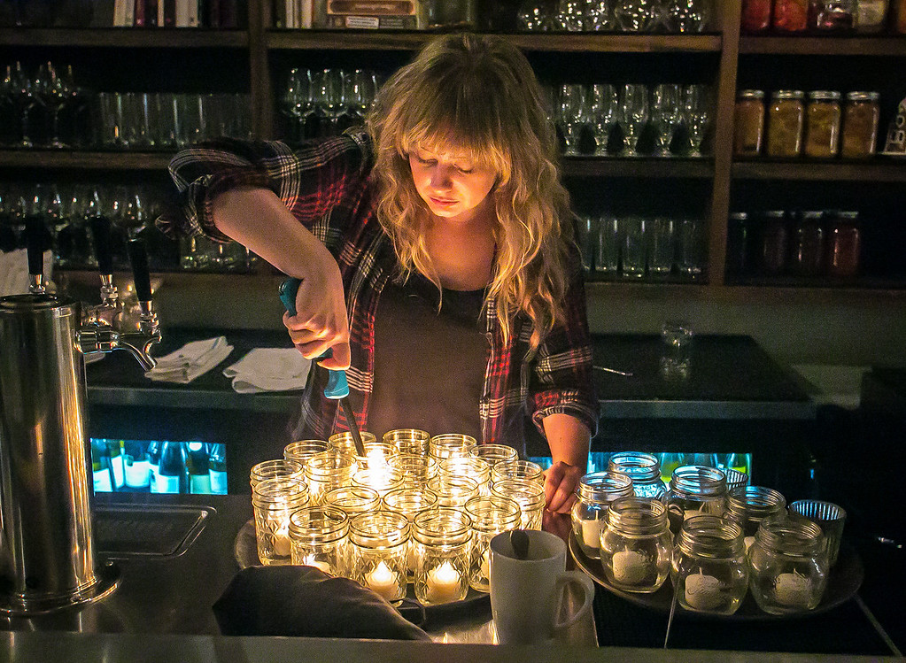 Bartender Sarah Elliott lights candles for the tables at St. Vincent restaurant in San Francisco, Calif., is seen on Friday, December 7th, 2012.