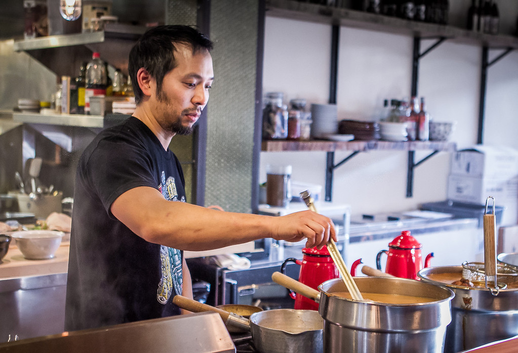 Chef Rayneil De Guzman checks the broths on the stove at the Ramen Shop in Oakland, Calif. on Friday, February 15th, 2013.