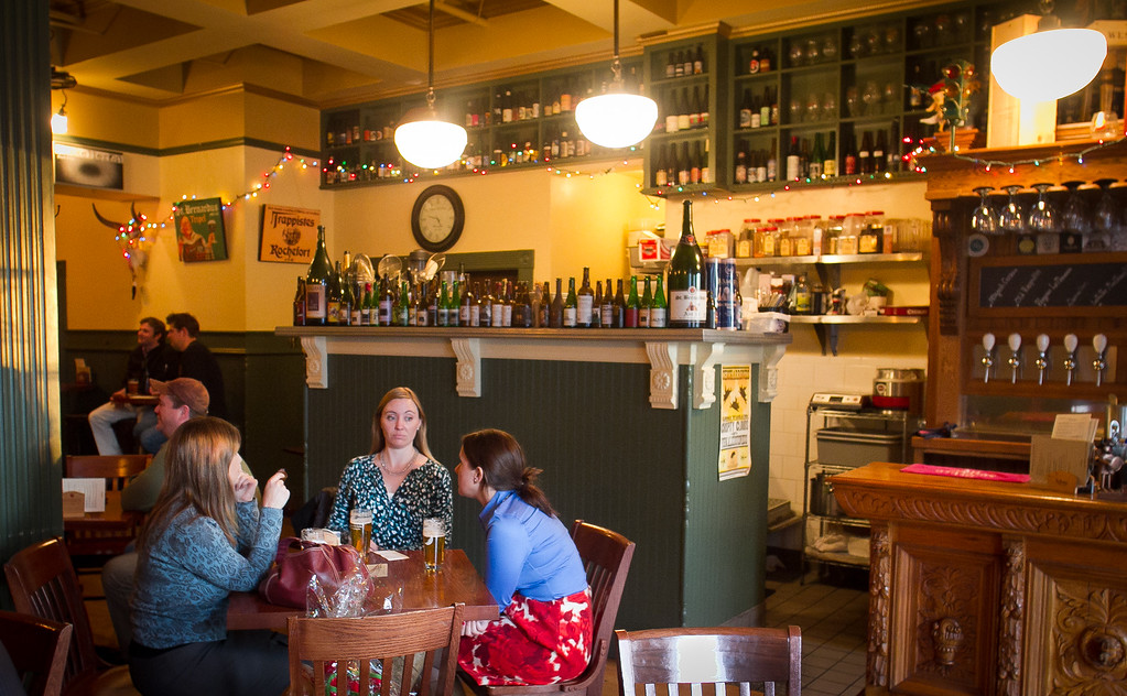 People enjoy beers during happy hour at the Trappist Bar in Oakland, Calif.,  on Tuesday, December 20th,  2011.