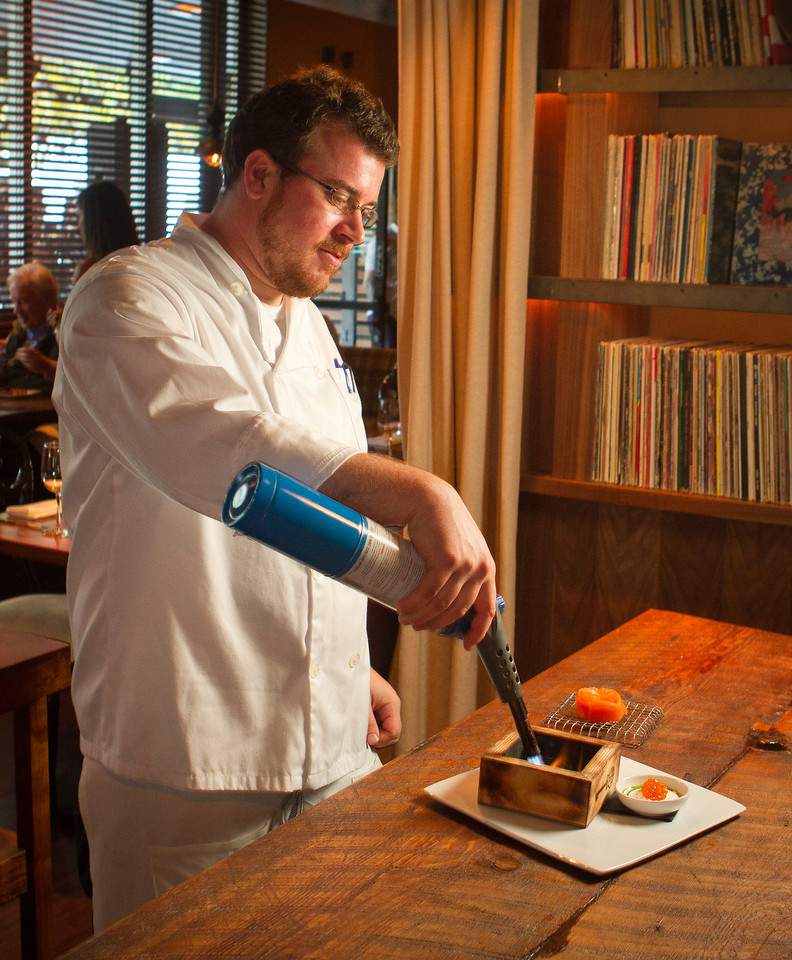 Chef Trevor Ogden lights wood chips with a torch for the Smoking Salmon appetizer at Chambers Eat + Drink restaurant in San Francisco, Calif., on August 30th, 2011.