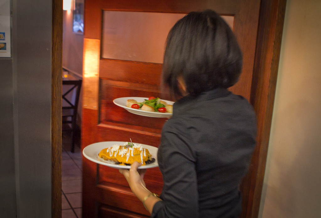 A server whisks food out of the kitchen at Cielito Lindo Restaurant in Napa, Calif.,  on Saturday, November 4,  2011.