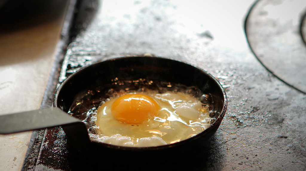 An egg frying on the flat top at Hawker Fare restaurant in Oakland, Calif., is seen on July11th, 2011.