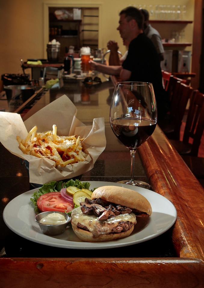 The Burger with Swiss and Mushrooms, Fries with Truffle Oil & Parmigiano-Reggiano and a glass of Pinot Noir at Healdsburg Bar & Grill in Healdsburg, Calif., is seen on July 22nd, 2011.