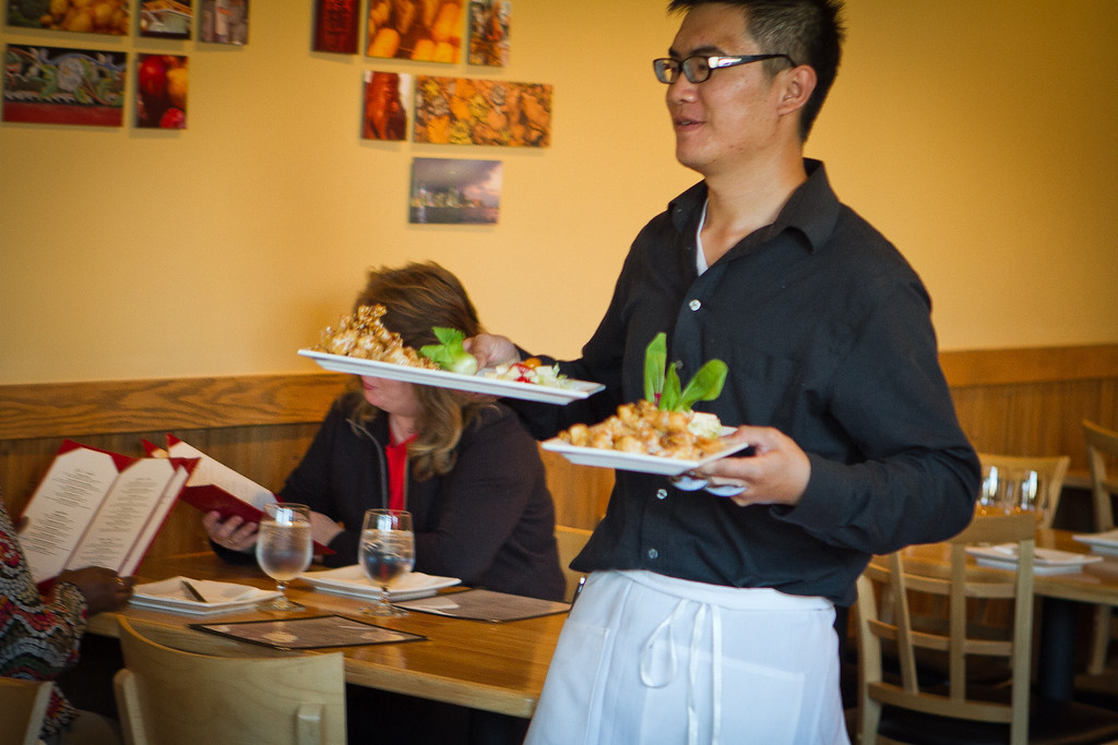 A waiter brings dishes to the table at Lin Jia Restaurant in Oakland, Calif., on Friday,  September 30th, 2011.