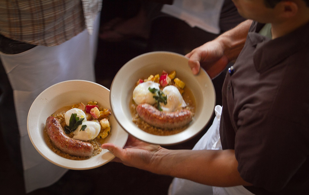 The wood grilled Sage and Garlic Sausage with poached eggs being carried to a table for brunch at Nopa in San Francisco, Calif., is seen on Sunday,  October 2, 2011.