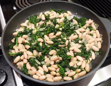 "White Beans and Spinach A deceptively ""plain jane"" looking dish that is REALLY good!!    Steam stir a large onion and 2 garlic cloves in a bit of broth or water till softened.  Add in 9 ounces spinach (or any other greens), 1/2 tsp. oregano and 1/4 tsp. salt and steam until wilted.  Add in a tablespoon of lemon juice and a can of white beans and stir till heated.  Dinner is ready in 15-20 minutes!!  I use this dish to use up whatever greens I have on hand ... especially useful during the summer CSA/Farmer's Market time.   I've used kale and bok choy at times, instead of spinach.  The bok choy works especially nicely, since its white stalks provide a nice crunch in this dish.  Adapted from a recipe by Robin Robertson in 1,000 Vegan Recipes."