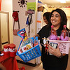 Food Fairy Mara Mercado of Lowell brings in gift baskets from the living room. At rear is Samantha Robinson of Lowell. (SUN/Julia Malakie)