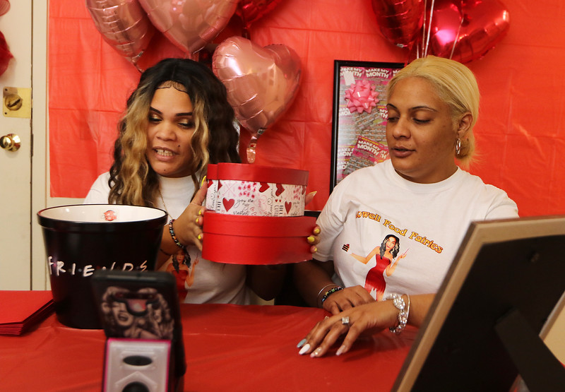 Food Fairies Margarita Silva, left, and Natasha Ramirez, right, showing gifts and announcing recipients during a livestream in Margarita's apartment. Both are from Lowell. Silva was drawing names out of the bucket for the Valentine's Day boxes, which contained chocolates and natural flowers. (SUN/Julia Malakie)