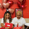 Food Fairies Margarita Silva, left, and Natasha Ramirez, right, showing gifts and announcing recipients during a livestream in Margarita's apartment. Both are from Lowell. (SUN/Julia Malakie)