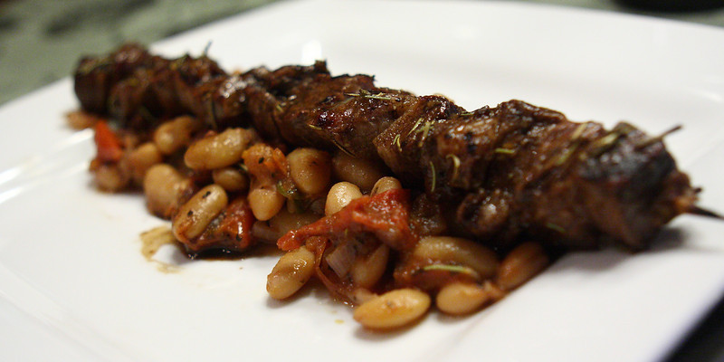 Balsamic Marinated & Grilled Lamb Kebobs on a Ragu of Garden Fresh Tomatoes & Cannelloni Beans with Jalapenos in a Red Wine Reduction.