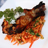 Tandoori chicken on a bed of Spicy Green Papaya & Carrot Salad, garnished with Yogurt sauce and cilantro.