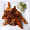 Crispy Fried Frog Legs on bed of rice topped with a Spicy Ginger Shallot Five Spice Sauce served with Green Grape Raita.