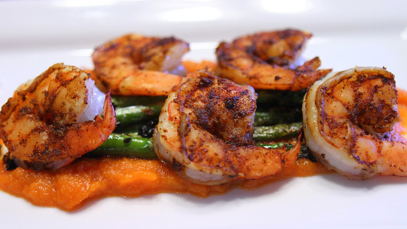 Ancho chili rubbed shrimp, cooked at the table on a hot salt plate, served with fresh from the garden asparagus, garlic and black sesame seeds sauteed in sesame oil, all served on a bed of carrot ginger puree.