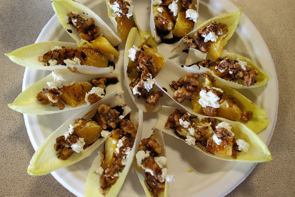 Endive filled with Orange, Honey Coated Walnuts, Goat Cheese, topped with a Balsamic Reduction. One of Nancy's signature appetizers.