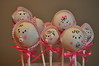 "Baby girl cake pops: candy pacifier, nose, cheeks, and bow. Chocolate chip ears. In cupcake liner ""bonnet"" with a ribbon bow"