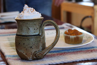 Homemade vegan whipped cream over coffee, in a mug made by artist Marsha Meyers.