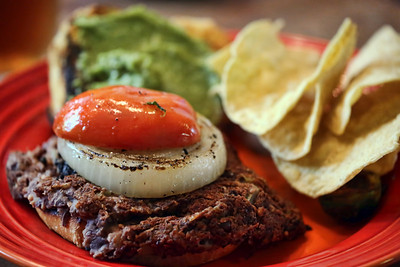 Grilled black bean burger with grilled veggies, along with guacamole and chips.