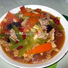 Sliced pork with mixed vegetables with crispy rice at the bottom of the plate