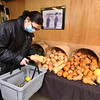 First time customer Julie Zanotta of Groton, who found out about the weekend market on Facebook, picks out butternut squash at the former Kirk farm at Wyman Road and Nashua Road in Groton, where Chad Spiczka sells fresh produce on Saturdays and Sundays through the winter. (SUN/Julia Malakie)