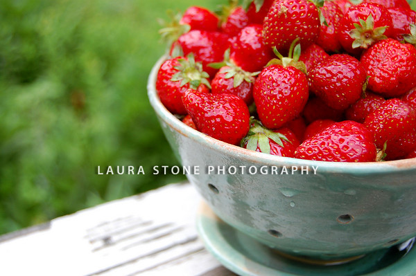 Fresh strawberries in a pottery colander