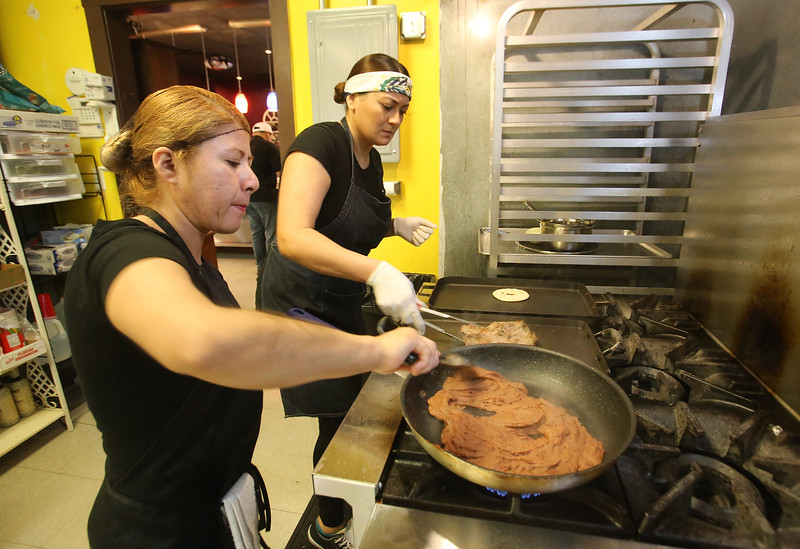 Lucia Echeverria of Lowell, front, cooks refried red beans filling for pupusas at Girasol Central American Food in Chelmsford. At rear is co-owner Marina Orellana of North Chelmsford. (SUN/Julia Malakie)