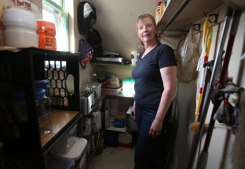 MaryBeth Bowen of Lowell, who has celiac disease, in her pantry, with some of the food and separate containers she needs to eat a gluten-free diet. (SUN/Julia Malakie)