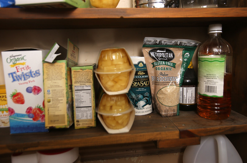 MaryBeth Bowen of Lowell, who has celiac disease, and the food, kitchenware and appliances she needs to eat a gluten-free diet. These are some items in her pantry. (SUN/Julia Malakie)