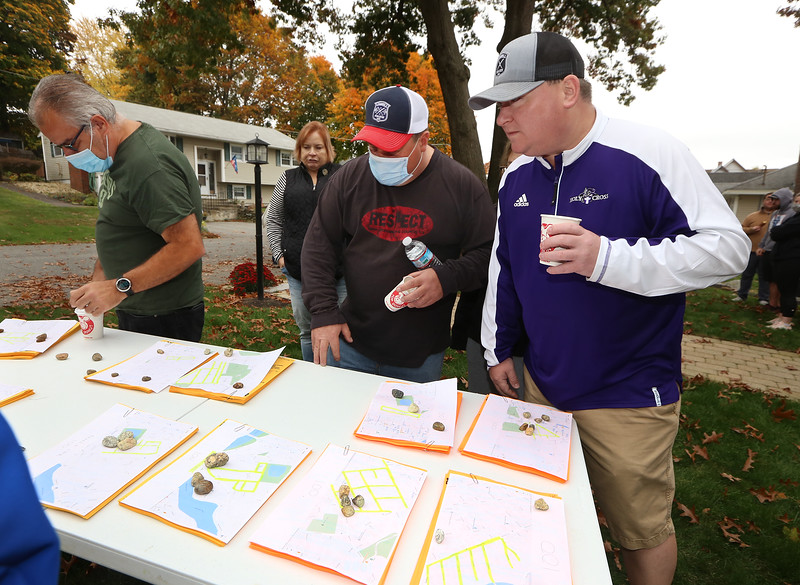 Volunteers pick up flyers to distribute to solicit donations for State Rep. Tom Golden's Halloween Food Drive Spooktacular, at Golden's house in Lowell. From left, David Burns, Lee Gitschier and Dan Dupras, all of Lowell, look over routes. (SUN/Julia Malakie)