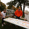 Volunteers pick up flyers to distribute to solicit donations for State Rep. Tom Golden's Halloween Food Drive Spooktacular, at Golden's house in Lowell. From left, Joe and wife Krista Petruzziello, Jeff Thomas, and Kathy Bedford, all of Lowell, look over walking routes. (SUN/Julia Malakie)