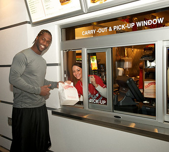 Mike Johnson from the Bengals gets carry out from Ruth Walker from the outdoor walk-up window at the new Johnny Rockets