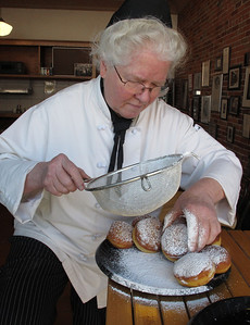 Judy Sarkozy dusts her paczki with sugar on March 1, 2011. In time for 'Fat Tuesday,' Sarkozy creates paczki in several varieties, raspberry, prune, lemon, custard, cherry, blueberry, apricot and unfilled, at her Sarkozy Bakery, 335 N. Burdick Street in downtown Kalamazoo, Michigan.  (Bradley S. Pines | CONTACT: bspines@gmail.com)