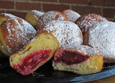 A raspberry paczek ($.85) is split, so the fruit filling may be seen on March 1, 2011. In time for 'Fat Tuesday,' Judy Sarkozy creates paczki in several varieties, raspberry, prune, lemon, custard, cherry, blueberry, apricot and unfilled, at her Sarkozy Bakery, 335 N. Burdick St. just north of the downtown Kalamazoo mall.  (Bradley S. Pines | CONTACT: bspines@gmail.com)