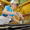 Ashley Davis, 22, a photo major at Fitchburg State University, scoops some ice cream at Kimball Farm, on Route 70 in Lancaster, when it opened Thursday to started serving ice cream for the new season. SENTINEL & ENTERPRISE/JOHN LOVE