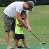 Kimball's Ice Cream in Westord, for story on area ice cream stands. Paul Shandrowski of Townsend helps his son Cam, 4, hit golf balls at the driving range. (SUN/Julia Malakie)