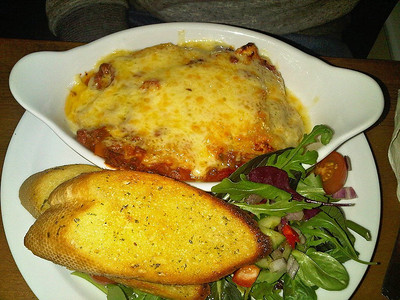 "Beef Lasagne - Prime Steak Mince with onions, mushrooms & peppers in a rich red wine bolognaise sauce interleaved with lasagne sheets topped with white sauce & melted cheese served with salad garnish & garlic bread. £8.45.  Served in ""The Penn Inn"" in Newton Abbot  17/12/13"