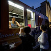 As might falls, customers Sierra Levine (lower left) and Olivia Elmasri order some chicken from Walloons Chicken truck at the Leominster Full Moon Food Truck Festival. SENTINEL&ENTERPRISE/ Jim Marabello