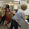 Volunteers Judy McDermott of Groton, left, and Wanda Burns of Lancaster, right, fill bags for pickup at Loaves & Fishes Food Pantry in Ayer.  SUN/Julia Malakie