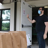 Volunteers at Loaves & Fishes Food Pantry in Ayer fill bags for pickup. Volunteer Cory Stasko of Littleton waves a car forward to pick up groceries. SUN/Julia Malakie