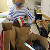 Volunteer Wanda Burns of Lancaster, fills bags for pickup at Loaves & Fishes Food Pantry in Ayer.  SUN/Julia Malakie
