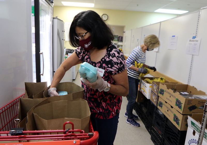 Volunteers Judy McDermott of Groton, left, and Wanda Burns of Lancaster, rear, fill bags for pickup at Loaves & Fishes Food Pantry in Ayer.  SUN/Julia Malakie